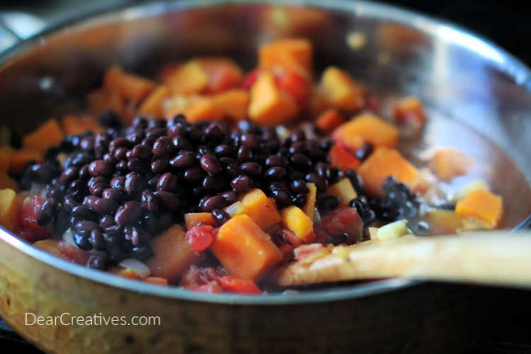 Adding black beans, tomato sauce to the skillet of vegetables for chili. DearCreatives.com