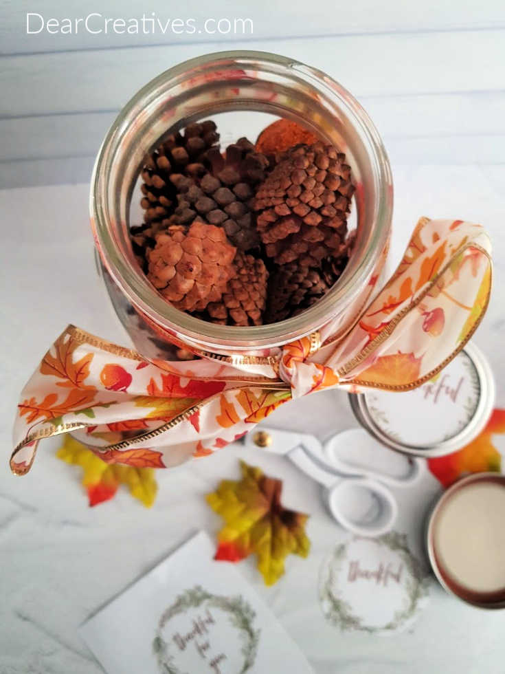 Adding the potpourri - scented pine cones to the mason jar craft for Thanksgiving. Easy craft tutorial and free printable at DearCreatives.com
