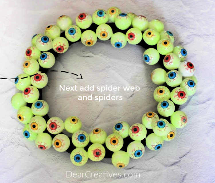 Eyeball Wreath - A wreath with eyeballs and spider web and spiders behind it to hang up for Halloween or spooky, fun parties. © DearCreatives.com