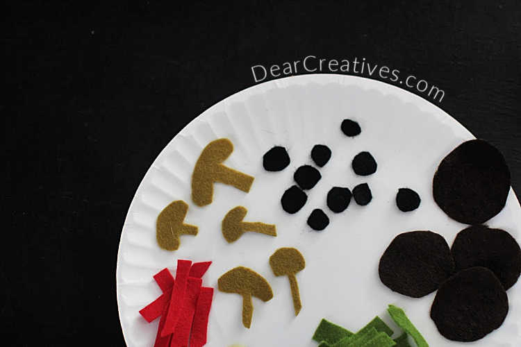 Food shapes cut from felt to make a felt pizza - mushrooms, pepperoni, olives, bell peppers, onions... DearCreatives.com