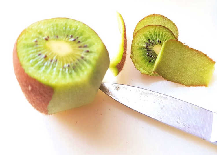 slicing the skin off a kiwi for a strawberry kiwi smoothie - DearCreatives.com