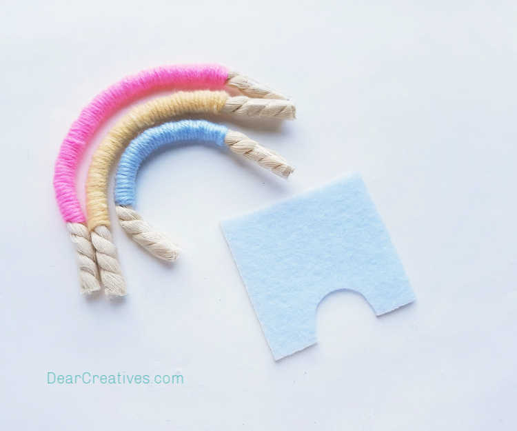 step (7) For Backing - Take a piece of the felt and cut an arch shape out of the felt from its bottom side. Macrame Rainbow instructions at DearCreatives.com.