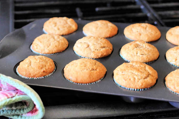 banana muffins batter scooped into muffin lined muffin pan - © DearCreatives.com