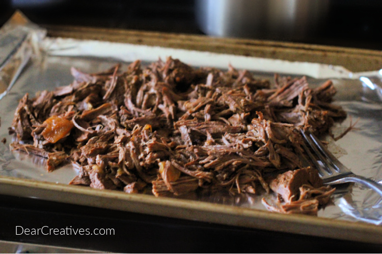beef barbacoa on a covered sheet pan before sauce is added to be broiled - © DearCreatives.com