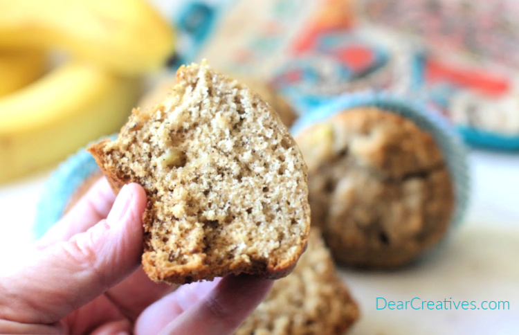 homemade banana muffins ready to be eaten - holding a cooled sliced banana muffin to eat - DearCreatives.com