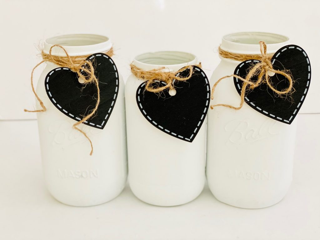 mason jars with heart tags tied on with twine - See how to make and style this craft project for your decor, farmhouse decor or for Valentine's Day mason jars...DearCreatives.com