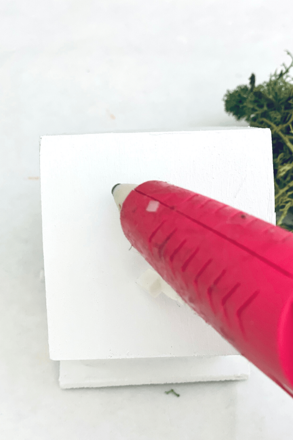 Adding hot glue to the back of the birdhouse to add to a pretty spring wreath -How-to at DearCreatives.com