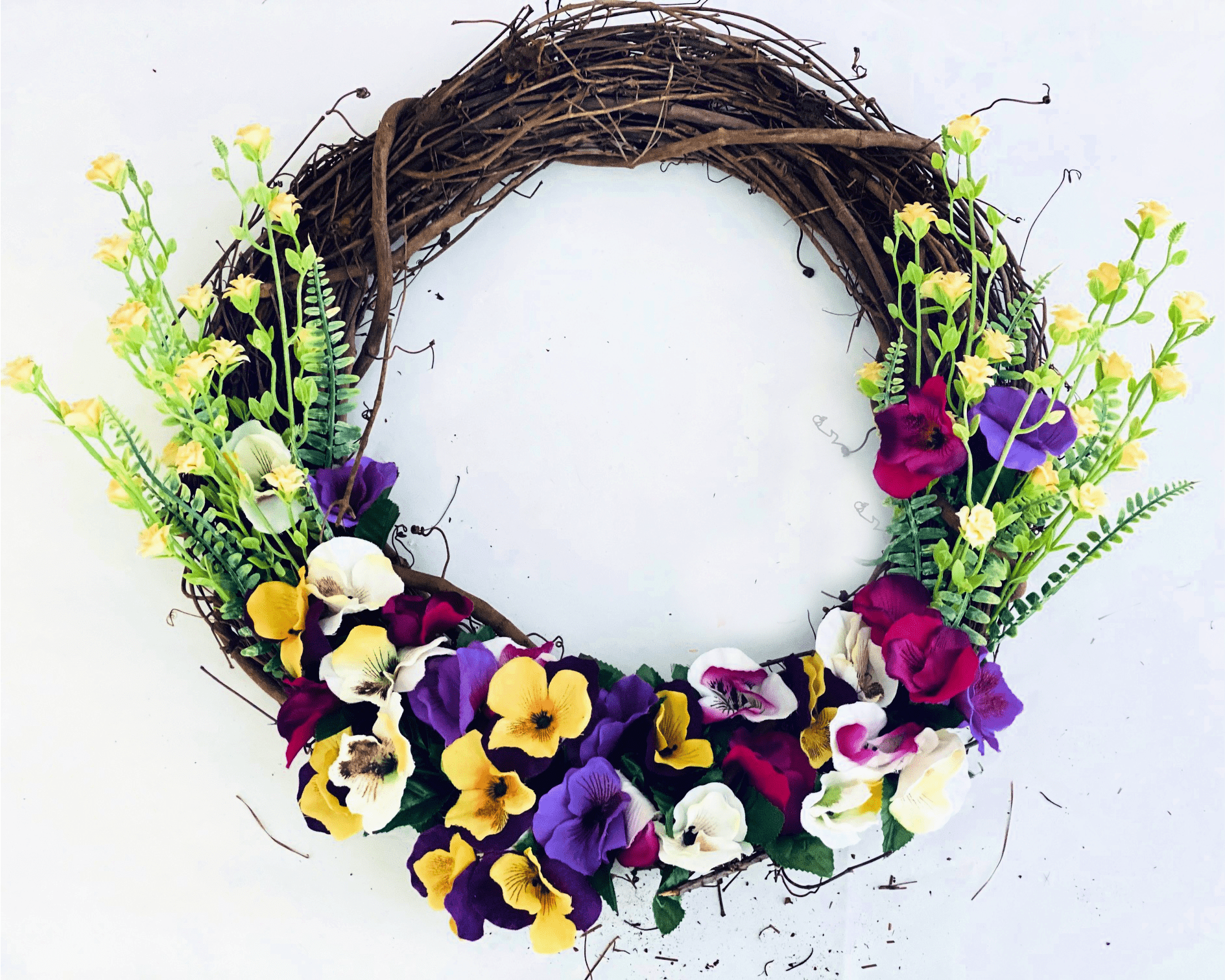 After adding artificial flowers (pansies in a variety of colors and yellow flowers with ferns) to the spring wreath. Next, add... DIY spring grapevine wreath at DearCreatives.com