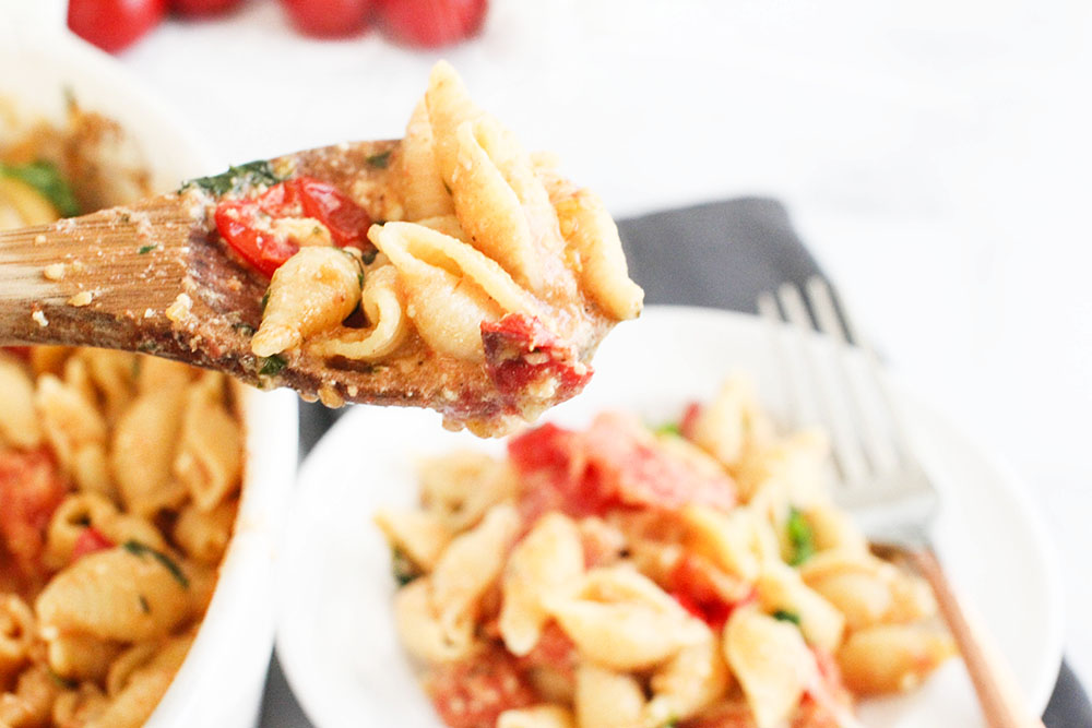 Baked feta pasta with tomatoes being served onto a plate - Get the recipe for feta pasta at © DearCreatives.com